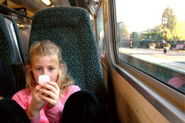 Muchacha que usa un teléfono móvil mientras que está en un tren.